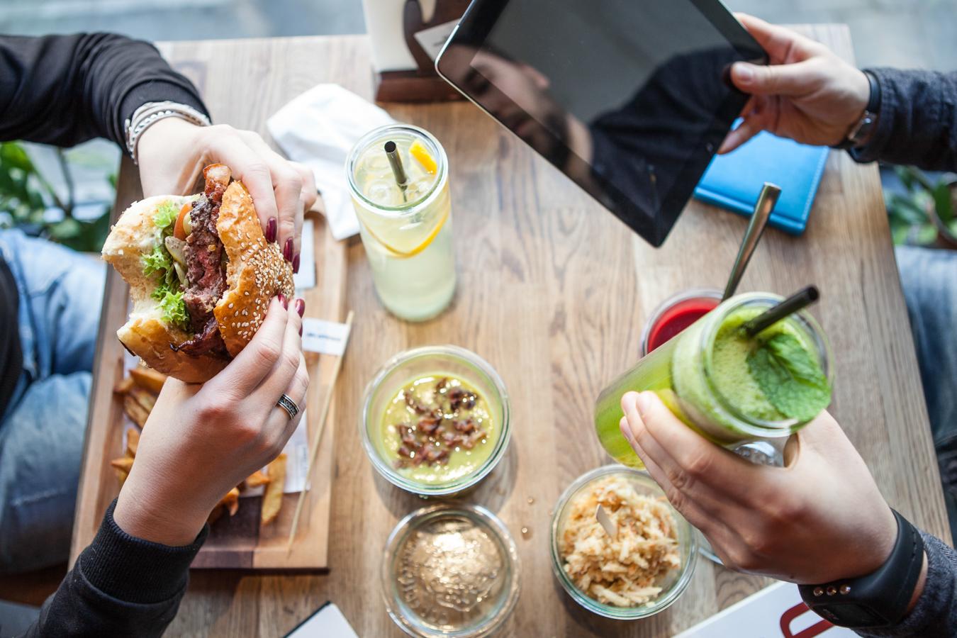 dwie osoby jedzą burgera i piją lemoniadę